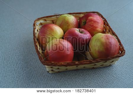 Red juicy apples in the basket on the table
