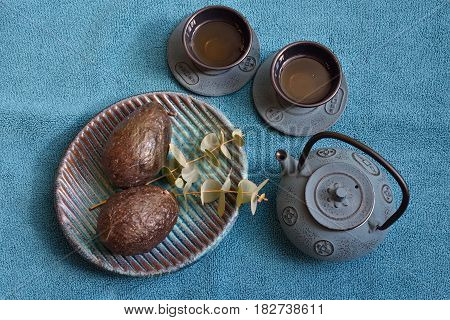 Turquoise background, topwiew. Marrakech style teapot and teacups, tea. plate with fresh avocados. Eucalyptus. Healthy and fresh breakfast or lunch. Foodphotography