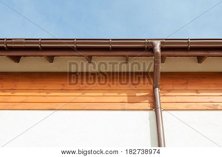 Close up on New Rain Gutter Downspout Soffit Board Fascia Board Installation Against Blue Sky