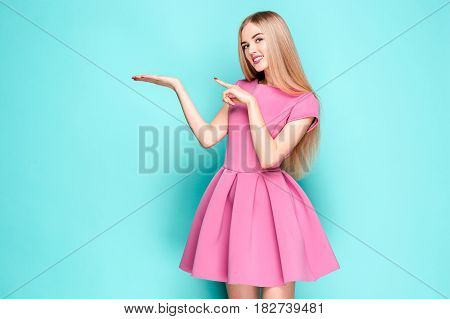 Smiling beautiful young woman in pink mini dress posing, presenting something and looking at camera. Three quarter length studio shot on blue background.
