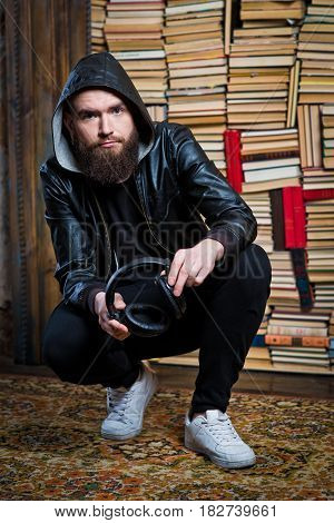 A bearded guy with headphones in his hands. The guy in the leather jacket. A bearded bald man. Man with big headphones