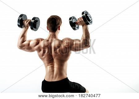 Sporty man in training pumping up muscles of the back and hands with dumbbells. Photo of strong male with naked torso isolated on white background. Strength and motivation.