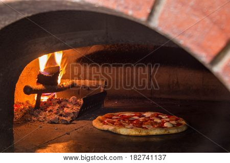 The wood furnace on firewood, for baking of pizza. Naked flame.