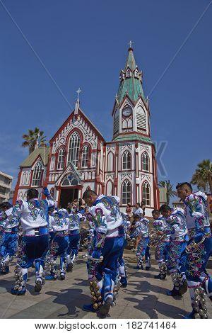 ARICA, CHILE - FEBRUARY 11, 2017: Caporales dancers in ornate costumes performing at the annual Carnaval Andino con la Fuerza del Sol in Arica, Chile.