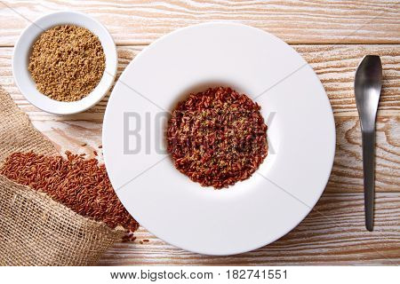 Red wild rice with sesame gomasio seasoning in a white plate over wooden board