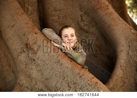 Blond kid girl smiling arms on big Ficus tree trunk