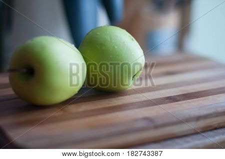 Two green apples lie on wooden cutting board