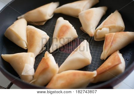 Many pancakes folded triangles on friyng pan almost top view