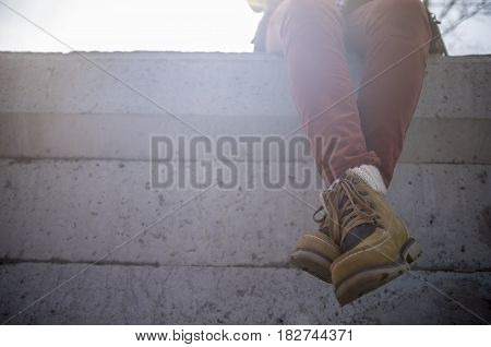 Stylishly dressed girl sits dangling and crossed her legs on a concrete fence in the warm rays of the spring sun.