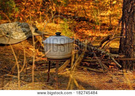 Cast-iron gray pot for an ear standing on a tripod near dry firewood