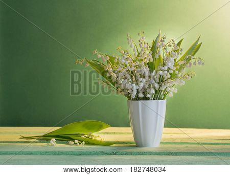 Lilly of valley in vase on green background
