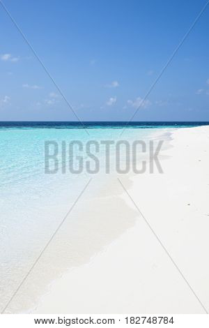 Ideal for summer vacation. Beach and white sand. The turquoise water of the ocean lagoon. Blue sky.