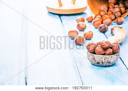Hazelnuts in shell scattered on blue plank table. Shelled nuts in wooden spoon