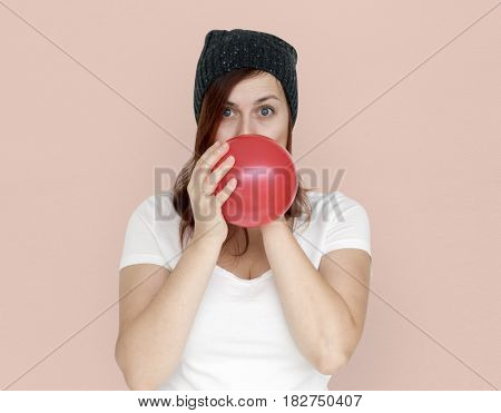 Woman Blowing Balloon Playful Studio Portrait