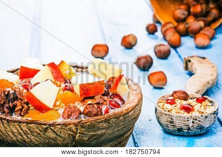 Homemade granola with apple in rustic wooden bowl and spoon. Hazelnuts and honey on the background