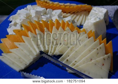 slices of assorted cheese Different kinds of cheese sliced and arranged on a platter