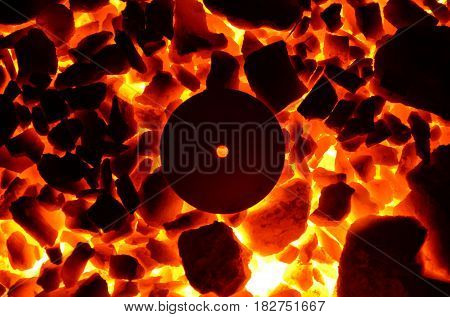 Burning coal and a red-hot metal circle with a hole.