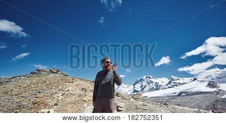 hiker at the top of a pass with radio enjoy sunny day in Alps. Switzerland, Trek near Matterhorn mount.