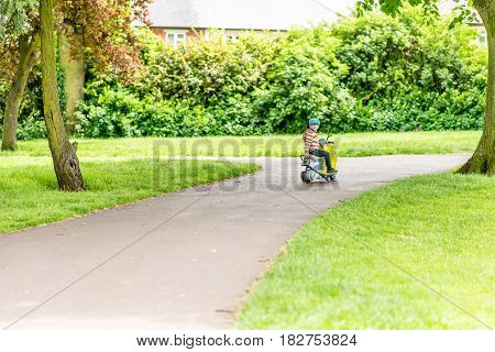 Day view child boy riding scooter summer park.