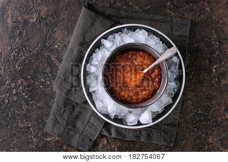 Bowl of red caviar on ice with spoon served with on black textile napkin over brown texture background. Top view with space