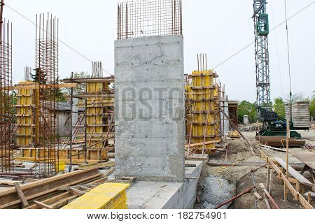 Concrete pillars supported with yellow boards and metal rods on construction site. Crane behind it.