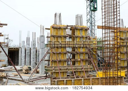 Concrete pillars supported with yellow boards and metal rods on construction site