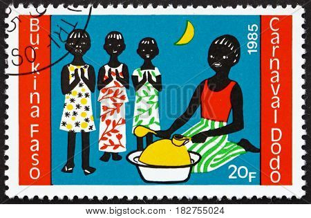 BURKINA FASO - CIRCA 1986: a stamp printed in Burkina Faso shows Three Children and Drummer Dodo Carnival circa 1986