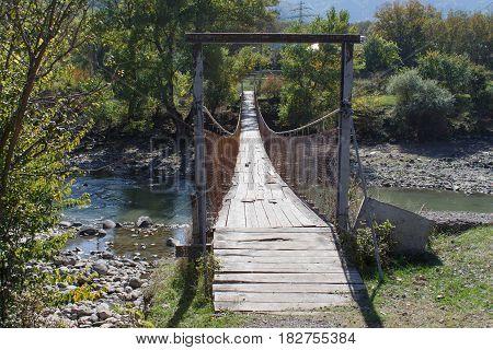 Old wooden bridge over the river. Pedestrian bridge. Wood and Iron Walking Bridge Over Rive