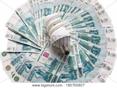 Energy saving bulb on the banknote background. The concept of energy saving