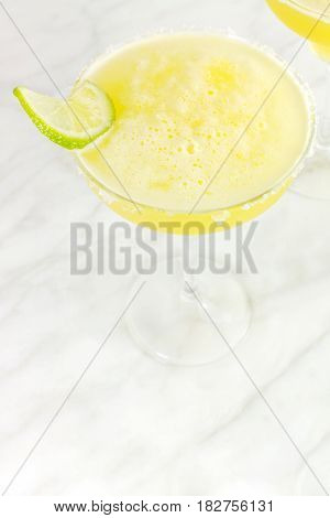 A high key closeup of a lemon Margarita cocktail with a wedge of lime, with a place for text. Selective focus