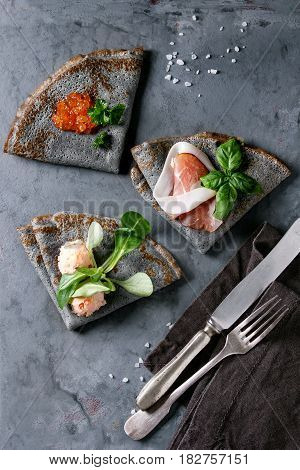 Black pancakes crepes with variety of salt filling red caviar, ham, fish salmon pate, green salad with vintage cutlery over gray texture metal background. Top view