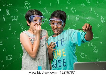 2 little indian kids doing chemistry experiment in classroom with safety eye glasses on standing over green chalkboard background with science doodles drawn over it