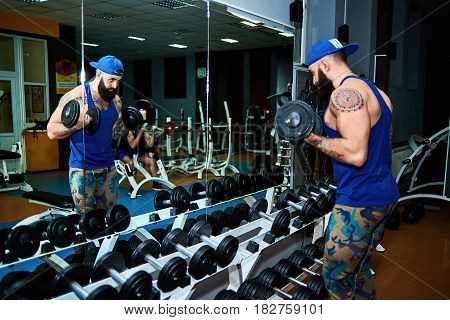 Handsome muscular young man exercising biceps in gym with dumbbells standing in front of the mirror