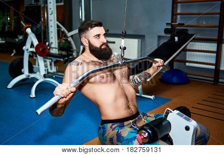 Muscular bearded man with tattoo training his back in gym
