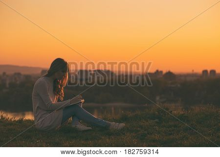 Woman enjoys writing at her notebook with a sunset over the city.