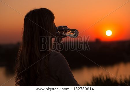 Silhouette of a woman drinking water at the sunset.