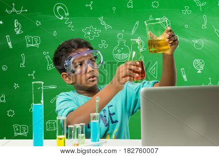 Kids and Science concept - Cute Indian little boy busy doing  science or chemistry experiment with test tube and flask with safety eye glass over green chalkboard background with science doodles drawn