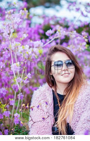 Happy girl in a pink fur coat in a blooming garden. Woman in sunglasses. Beautiful girl in an artificial fur coat. A girl with long hair smiles.