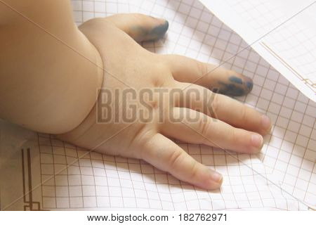 The hand of a small child is stained in ink lying on a piece of paper. Can be used as a concept of a beginner in business an illiterate compilation of a business plan