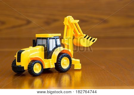 Children's Tractor Yellow On A Brown Background