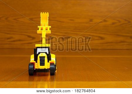 Children's Tractor Yellow With A Raised Bucket On A Brown Background