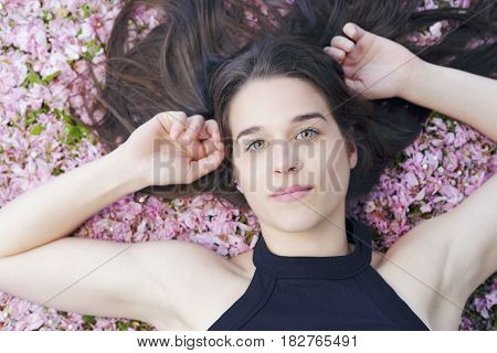 Young Woman Lying On A Ground Covered With Pink Flowers.