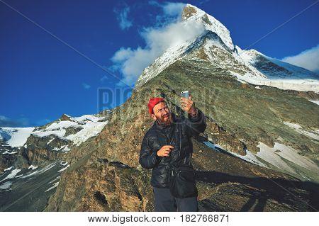 hiker at the top of a pass making selfie against the Matterhorn mount, Switzerland