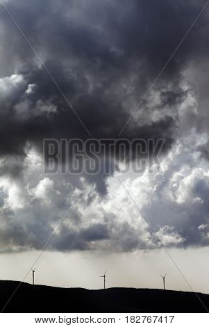 Silhouette Of Wind Farm And Cloudy Sky Before Storm