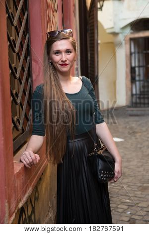 Modern young woman on the street of old europian city