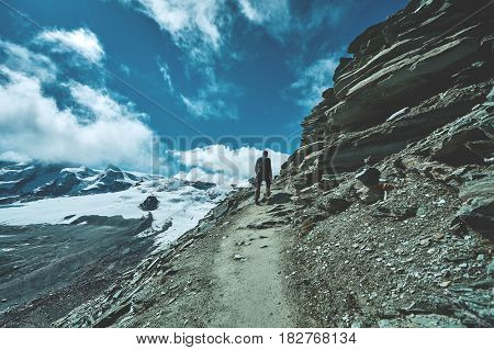 hiker on the trail in the Alpine mountains with backpack enjoy sunny day in Alps. Switzerland, Trek near Matterhorn mount.