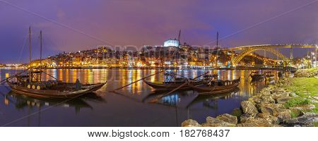 Panoramic view, traditional rabelo boats with barrels of Port wine on the Douro river, Ribeira and Dom Luis I or Luiz I iron bridge on the background, Porto, Portugal.