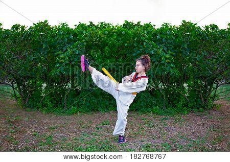 Girl in a Taekwondo uniform on nature background