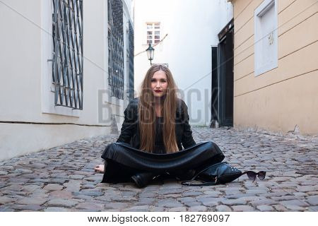 Modern young woman sitting in the street of old europian city