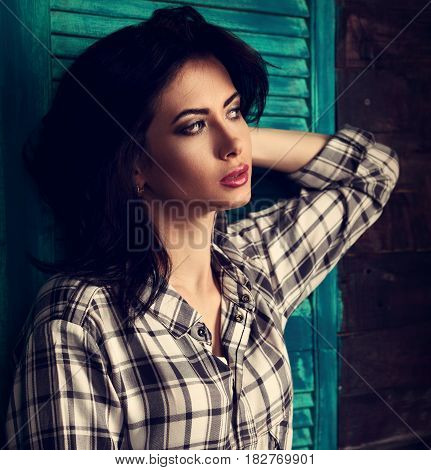 Beautiful Makeup Woman In Trendy Black And White Checkered Shirt Thinking On Blue Wooden Background.